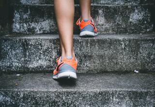 Feet running up concrete steps