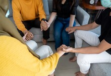 People supporting each other holding hands   suicide prevention