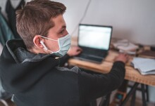Student in mask studying web