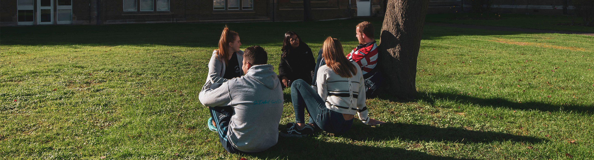 A picture of some students sitting and chatting on a sunny day on our campus