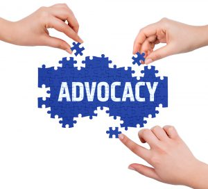 Advocacy Image - Image shows a jigsaw puzzle with the word advocacy on it and three hands with jigsaw pieces adding them to the puzzle.