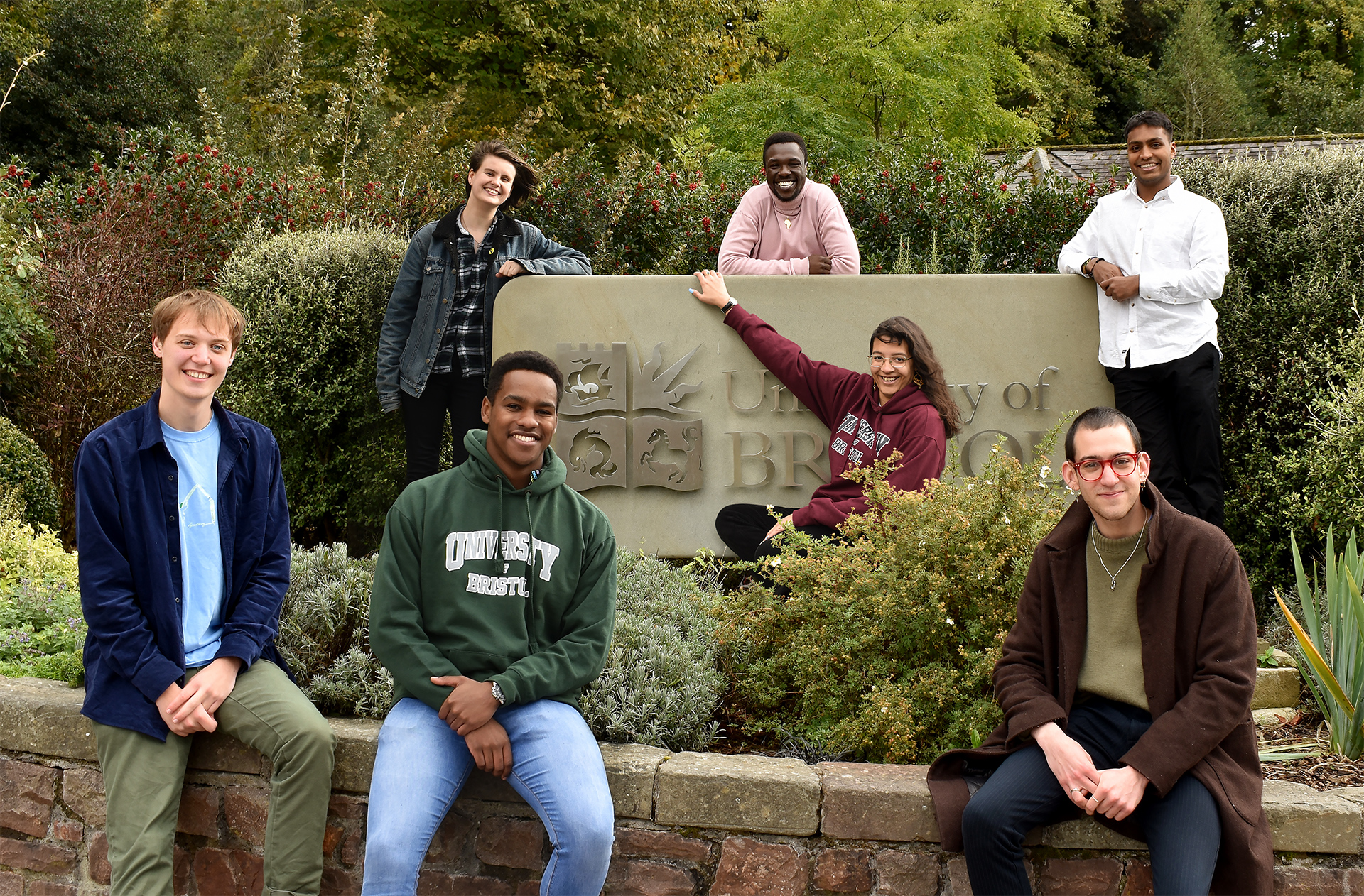 Photo of Bristol SU Officers sat outside surrounding a stone 'University of Bristol' Logo. From Left to Right is David Ion, Ruth Day, Roy Kiruri, Julio Mkok, Leah Martindale, Jason Palmer, and Rushab Shah.