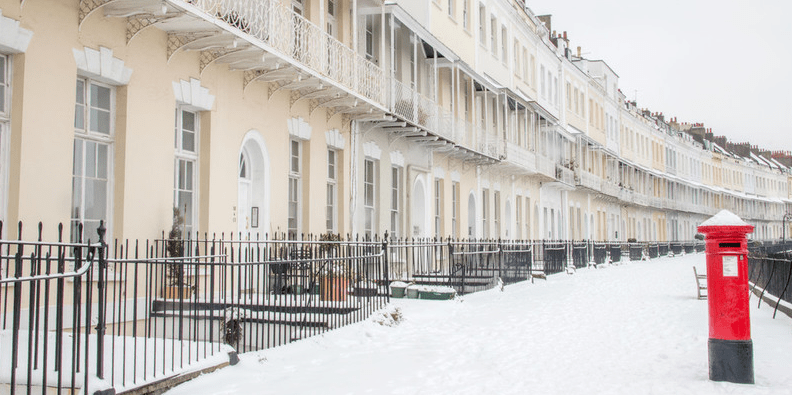 Royal York Crescent in snow. On the right in the foreground is a red Royal Mail postbox.