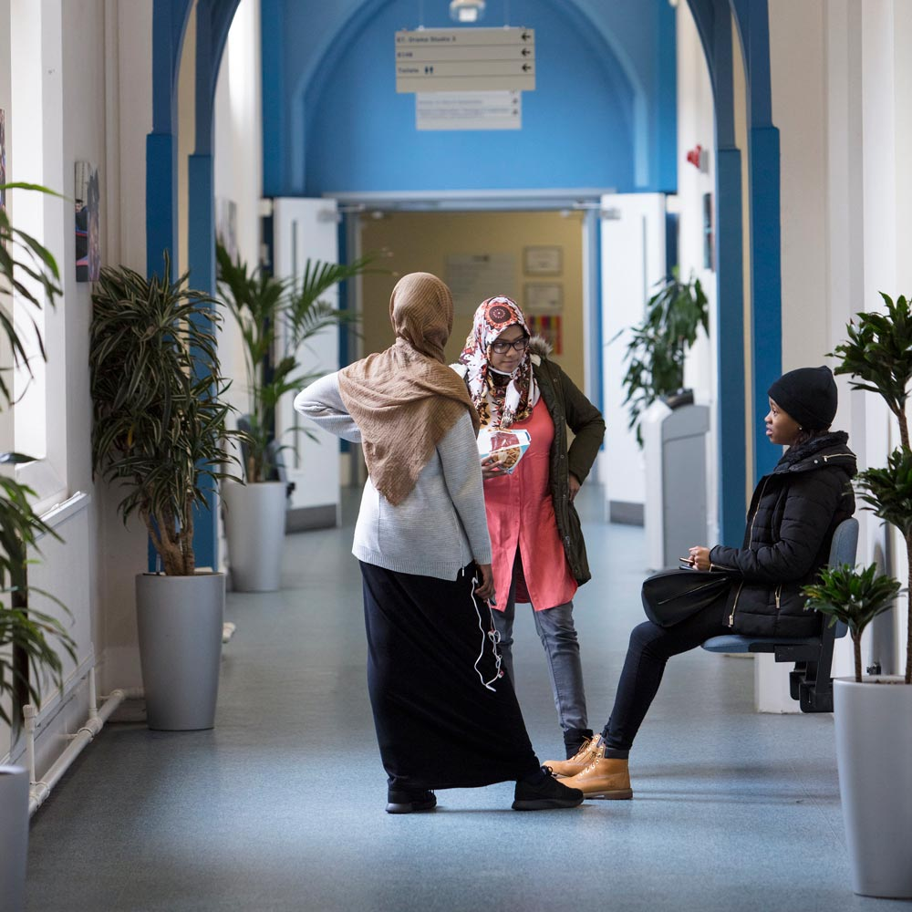 An image of some St Mary's students chatting in a corridor on campus before a lecture