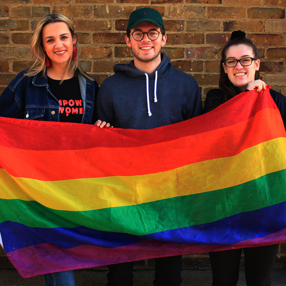3 students with a rainbow flag