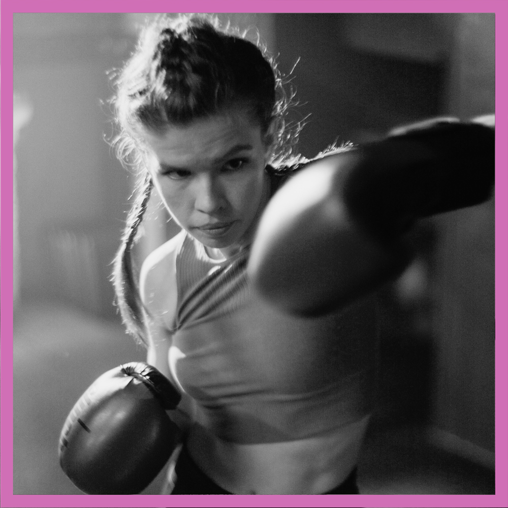 A woman boxing at a gym with gloves on