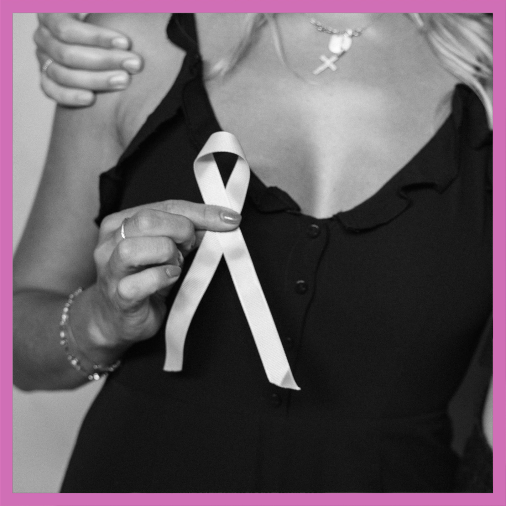 A woman's breasts with a pink breast cancer awareness ribbon over them