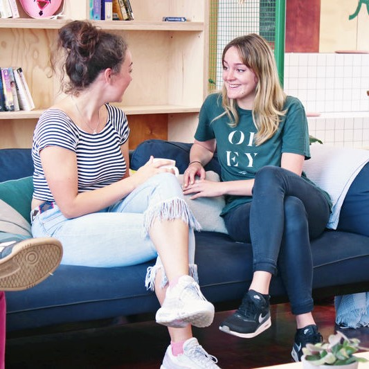 Photo of two students sat in The Bristol SU Living Room