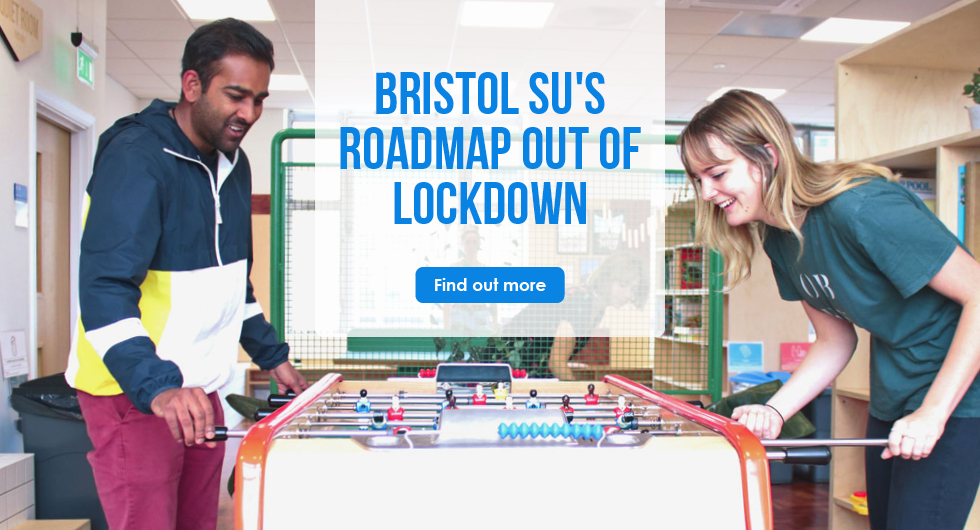 """Two students play table football in the Bristol SU Living Room. A translucent rectangle is overlaid on top with blue text; """"Bristol SU's roadmap out of lockdown. Find out more."""""""