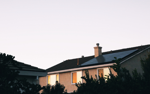 A photo of a house with solar panels on the roof, behind some trees.