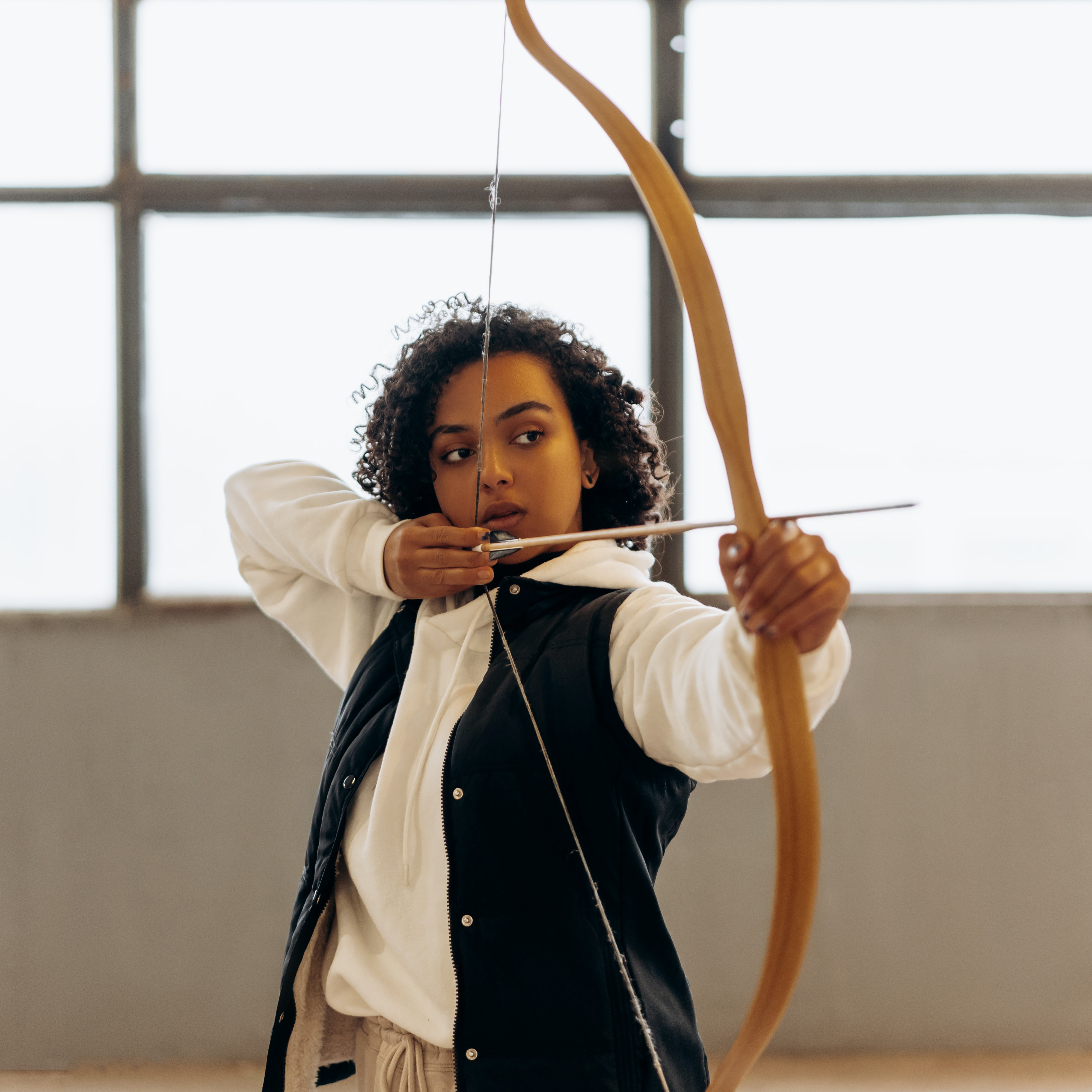 A student drawing their bow and arrow
