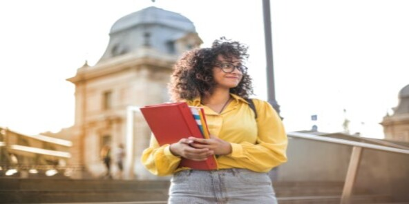 Student carrying paperwork 592 x 296